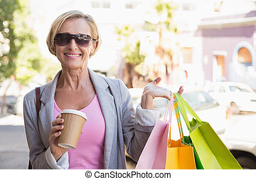 Happy mature woman walking with her shopping purchases on a...