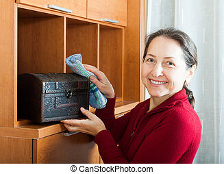 Happy mature woman wiping dust from chest