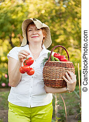 woman with basket of harvested vegetables