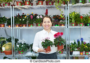 mature woman with Cyclamen plant
