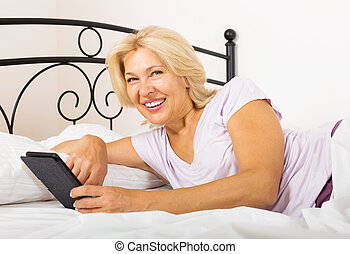 Happy mature woman with eBook