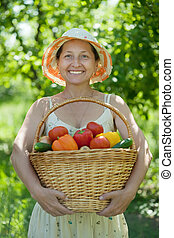 Happy mature woman with harvested vegetables