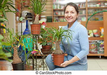 Happy mature woman with Nolina plant