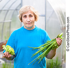Happy mature woman with onion and lettuce in front of the greenhouse