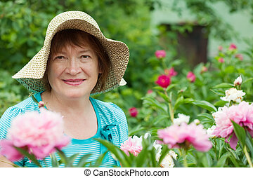 Happy mature woman with peony plant