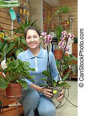 Happy mature woman with Phalaenopsis