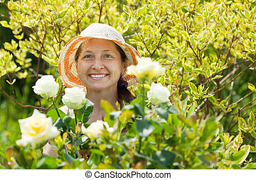 Happy Mature woman with roses plant