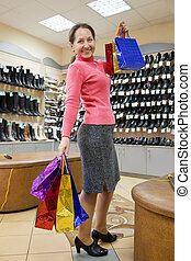 woman with shopping bags at shoes shop