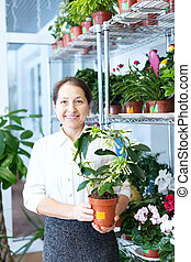 Happy mature woman with Stephanotis