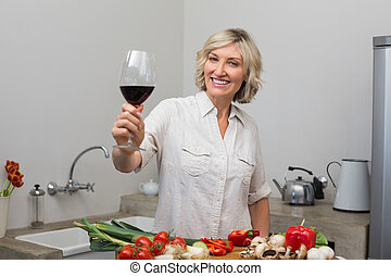Happy mature woman with vegetables and wine glass in kitchen