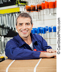 Happy Mature Worker Leaning On Tool Package