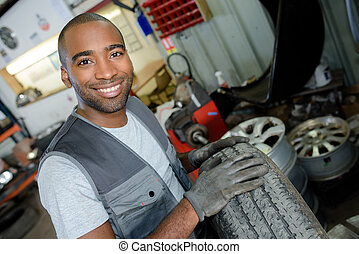 happy mechanic carrying a tire in tire service