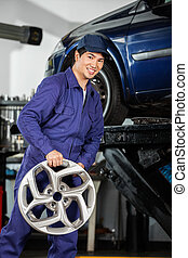 Happy Mechanic Holding Alloy At Repair Shop