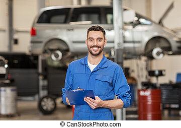 happy mechanic man with clipboard at car workshop - car...