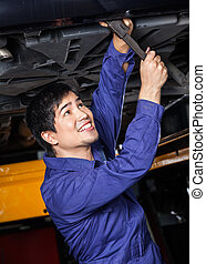 Happy Mechanic Working Underneath Car