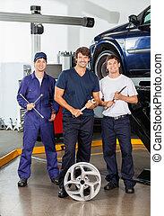 Happy Mechanics Holding Worktools At Garage