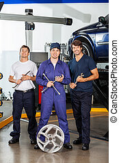 Happy Mechanics Holding Wrenches At Garage