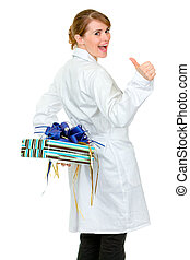 Happy medical doctor woman holding gift behind her back and...
