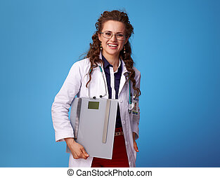 happy medical doctor woman with scales on blue