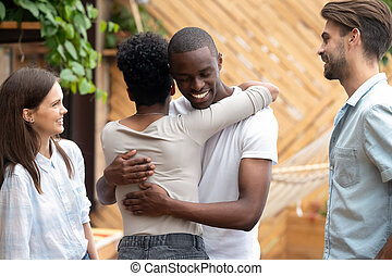 Happy meeting of African American couple embracing in cafe