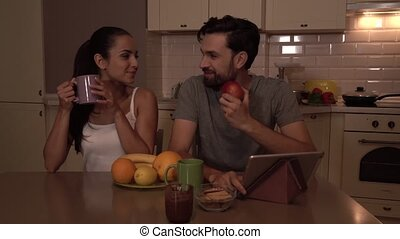 Happy members of small family sits at table. Girl drinks from cup. Guy eats apple. There are tablet and busket with fruit stand on table. They are smiling to each other. Girl leans to guy.