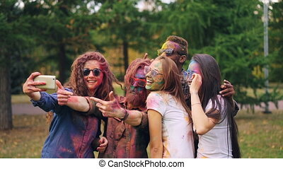 Happy men and women friends with painted faces and hair are taking selfie at Holi festival using smartphone camera, people are posing and smiling. Fun and technology concept.