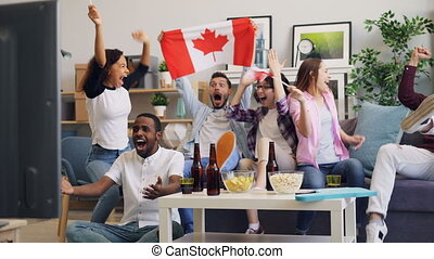 Happy men and women with Canadian flags watching sport on TV...