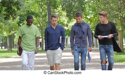 Happy men students walking together on campus. slow motion