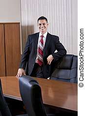 Happy mid-adult Hispanic businessman in boardroom