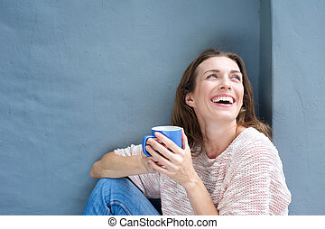 Happy mid adult woman laughing with a cup of tea