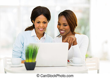 mid age african mother and daughter using laptop computer