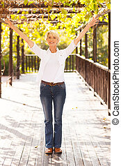 mid age woman with arms outstretched