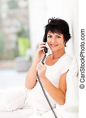 mid aged woman talking on landline phone - happy mid aged ...