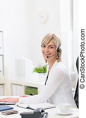 Happy middle age business woman with headset working at office