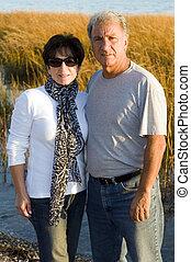 happy middle age senior couple on beach