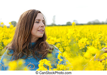 Happy middle age woman in yellow field