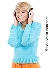 Happy middle age woman listening music in headphones