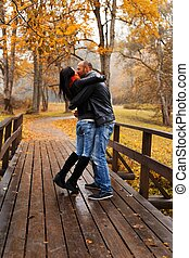 Happy middle-aged couple kissing outdoors on beautiful autumn day
