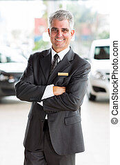 middle aged man working at car dealership