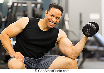 middle aged muscular man holding dumbbell