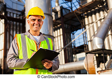 happy middle aged oil industry worker in refinery plant