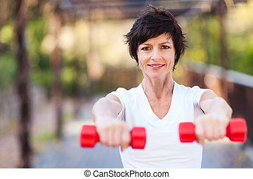 happy middle aged woman exercise with dumbbells outdoors