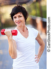 middle aged woman exercise with dumbbells