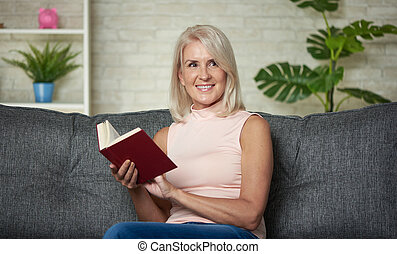 Happy middle aged woman is reading a book at home