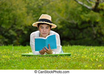 Happy middle aged woman lying on green grass reading a book in the park