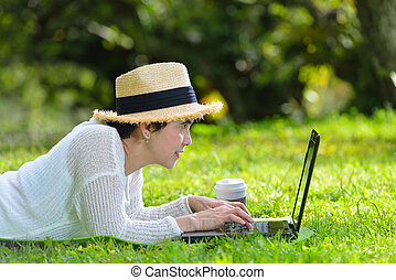 Happy middle aged woman lying on green grass using laptop computer in the park