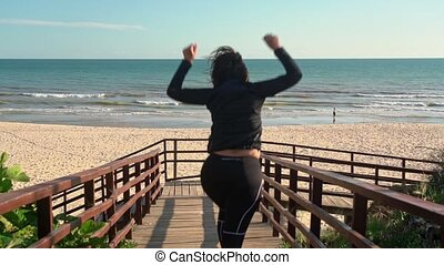 Happy middle aged woman runs on a wooden walkway to the ocean. Slow motion
