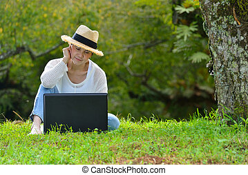 Happy middle aged woman sitting on green grass using laptop computer in the park