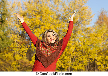 Happy middle aged woman with arms outstretched