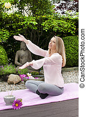 Happy middle aged woman with arms outstretched in zen garden